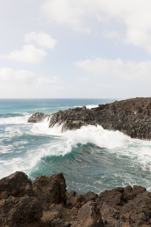 View of crashing waves, Los Hervideros, Lanzarote with soft white clouds in sky and lava rocks to foreground.