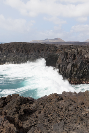 playa blanca: Large crashing waves hitting rocks at Los Hervideros, Lanzarote with a blue sky and mountains to the distance. Stock Photo