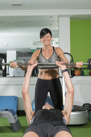 Female Gym Trainer Spotting For A Man Doing Bench Press Stock Photo    86774092