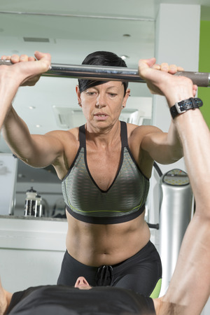Stock Photo   Woman Fitness Trainer Spotting For Man Performing Bench Press