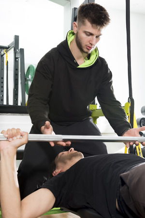 Fitness Coach Spotting For A Man Doing Barbell Bench Presses Stock Photo    86774113