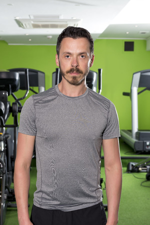 Fit man standing in front of cardio equipment in a gym
