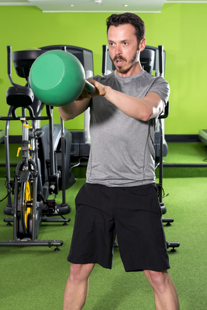 Athletic man focused on his kettlebell workout in a gym