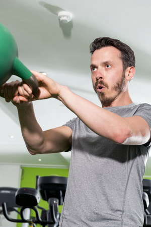 Ahtletic man working out using a green kettlebell