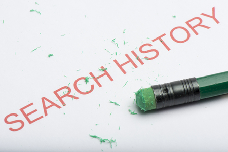 The word search history on paper with worn pencil eraser and eraser shavings. Concept of removing, deleting or untracing web browsing search history, covering tracks.