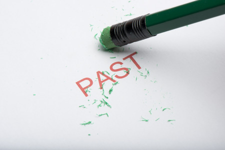 The word past on paper with worn pencil eraser and eraser shavings. Concept of forgetting or changing history or past, removing memories Stock Photo