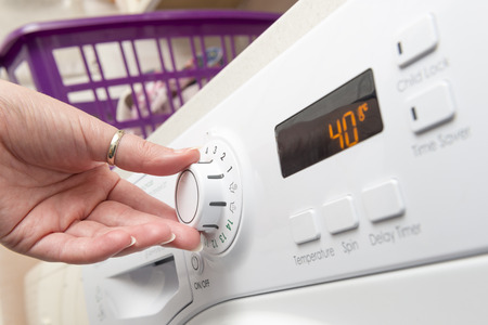 Hand adjusting the settings knob of a clothes dryer