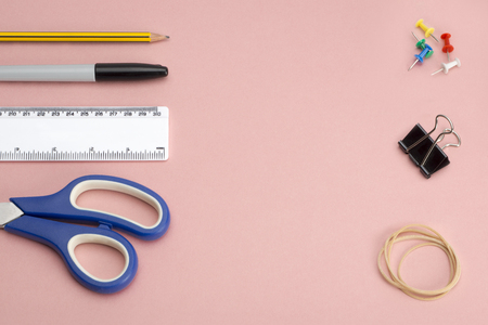 foldback: Various office or school supplies and tools including a pair of scissors, ruler, marker pen, a pencil, push pins, a binder clip and rubber band on a pink background with copy space