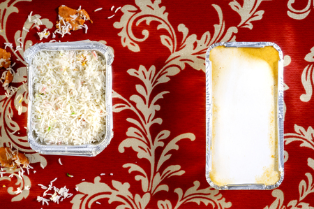 Overhead view of cooked rice and gratin in foil trays on a red floral background