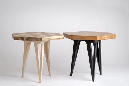 Twee moderne houten salontafels met zeshoekige bladen, waarvan een met geverfde zwarte poten Stockfoto