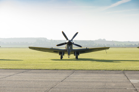 Front view of a classic spitfire aircraft parked by the side of a runway