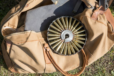 Rifle ammunition in a round case laid on an old tote bag