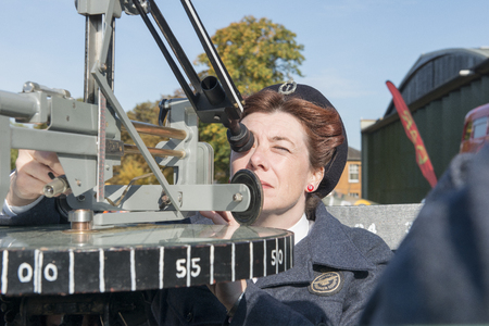 Lady military personnel peering through a post plotting instrument outdoors