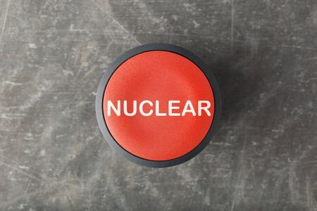 Overhead of a red circular 'nuclear' push button on a concrete background Stock Photo