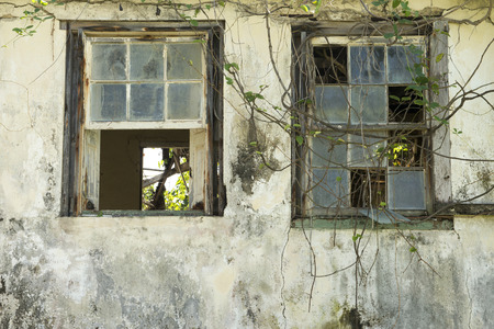 Two broken windows of a dilapidated building or house