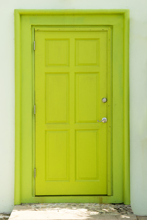 Painted green closed door installed on a white wall Stock Photo