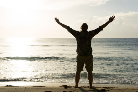 silhouette of a man with outstretched arms and facing the sun