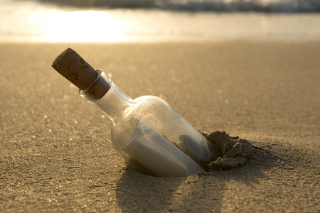 Message in a bottle half-buried in sand Stock Photo