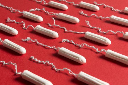 Close up of rows of tampons on a red background Reklamní fotografie