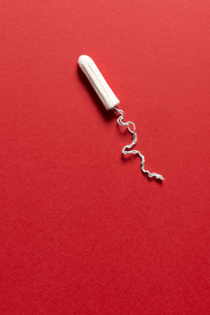 Unused tampon on a red background with copy space Stock Photo