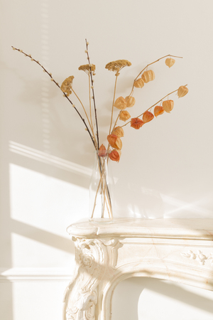 Clear glass vase containing dried blooms placed on a fireplace mantel by a white wall