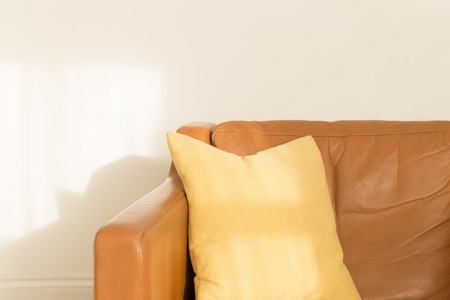 Square pillow on a brown leatherette armchair over a white wall background Stock Photo