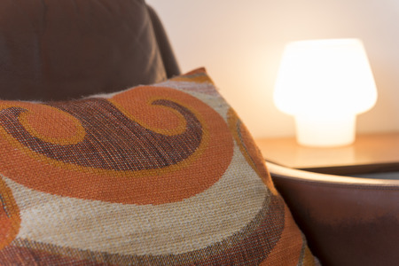 Pillow on leather armchair with illuminated desk lamp in the background
