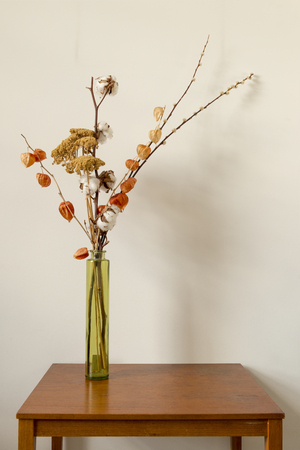 Cylindrical Glass Vase With Dried Flowers On A Wooden Surface