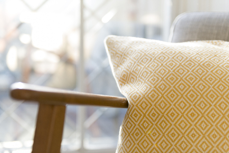 Close up shot of a pillow by the armrest of a vintage wooden chair Stock Photo