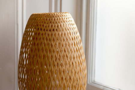 Wicker woven lampshade beside a window Banque d'images
