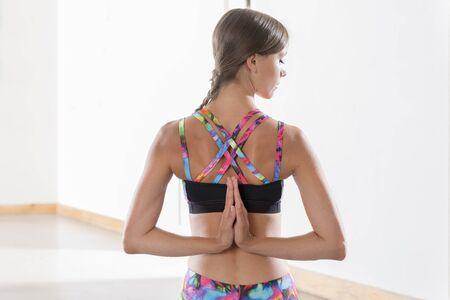 Young woman doing a revesre prayer yoga pose