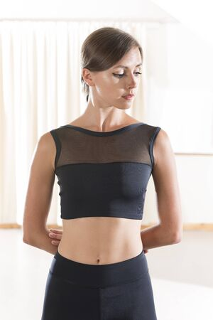 Portrait of a young woman wearing a black sports crop top and matching pants