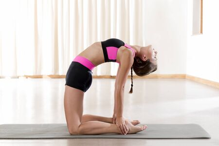 Fitness lady kneeling while bending backward on mat, stretching, warm-up