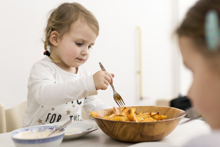 Little girl picking fried potato wedges up from a bowl using a fork Stock Photo