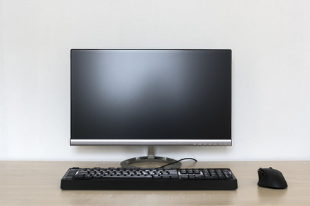 Computer monitor, keyboard, and a wireless mouse on desk 版權商用圖片