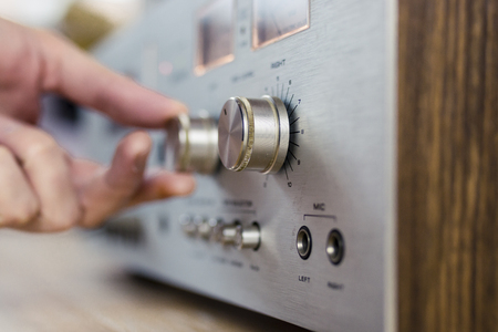 Hand turning a dial on a vintage home stereo equipment Banco de Imagens