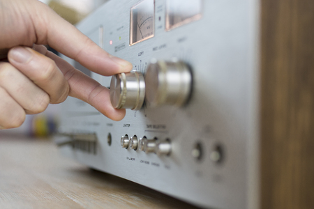 Hand cranking a dial on a vintage home stereo equipment