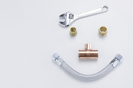 An adjustable spanner, nuts, a copper joint, and a flexible pipe forming a smiley face on white background with copy space