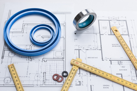 Folding rule, washers, and pipe seal rings on a building plan background