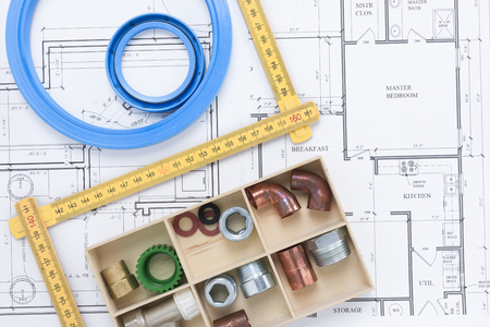 Various pipe fittings and a folding rule on a building plan background flat lay Stockfoto
