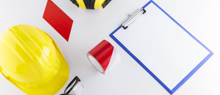 Hard hat, goggles, barricade tape, earmuffs, and clipboard on white background banner image