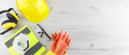 Banner image of construction safety gear including a hard hat, folded reflective jacket, face mask, goggles, and rubber gloves flat lay on white wooden surface with copy space Stock Photo
