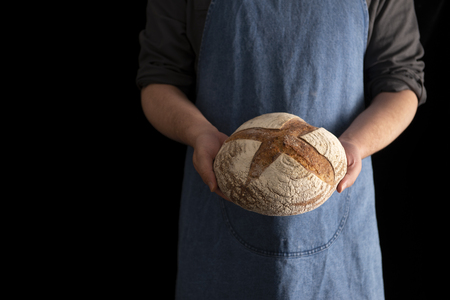 Baker with sourdough rye bread in hand on black background with copy space