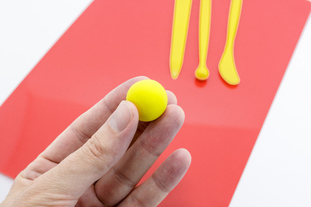 Hand holding a ball of yellow soft clay with crafting tools in the background