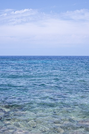 Clear ocean waves under cloudy blue sky in portrait orientation