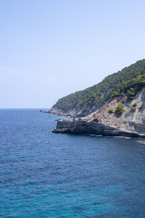 Tranquil blue ocean by the foot of a Mallorca limestone mountain