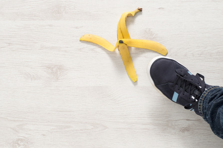 Overhead view of a foot about to step on a banana peel
