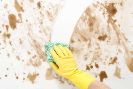 Gloved hand wiping clean a messy counter top or floor with a cloth or rag Imagens