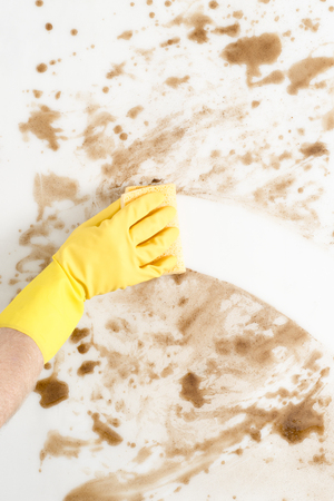 Hand wearing a glove wiping a dirty counter or floor with a sponge