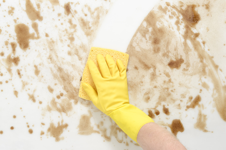 Gloved hand wiping a dirty counter top or floor with a yellow sponge Imagens